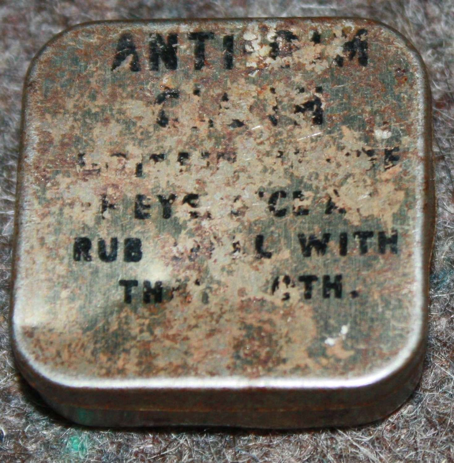 A SMALL SIZED DIMISTING TIN AND CLOTH 1 INCH SQUARE TIN