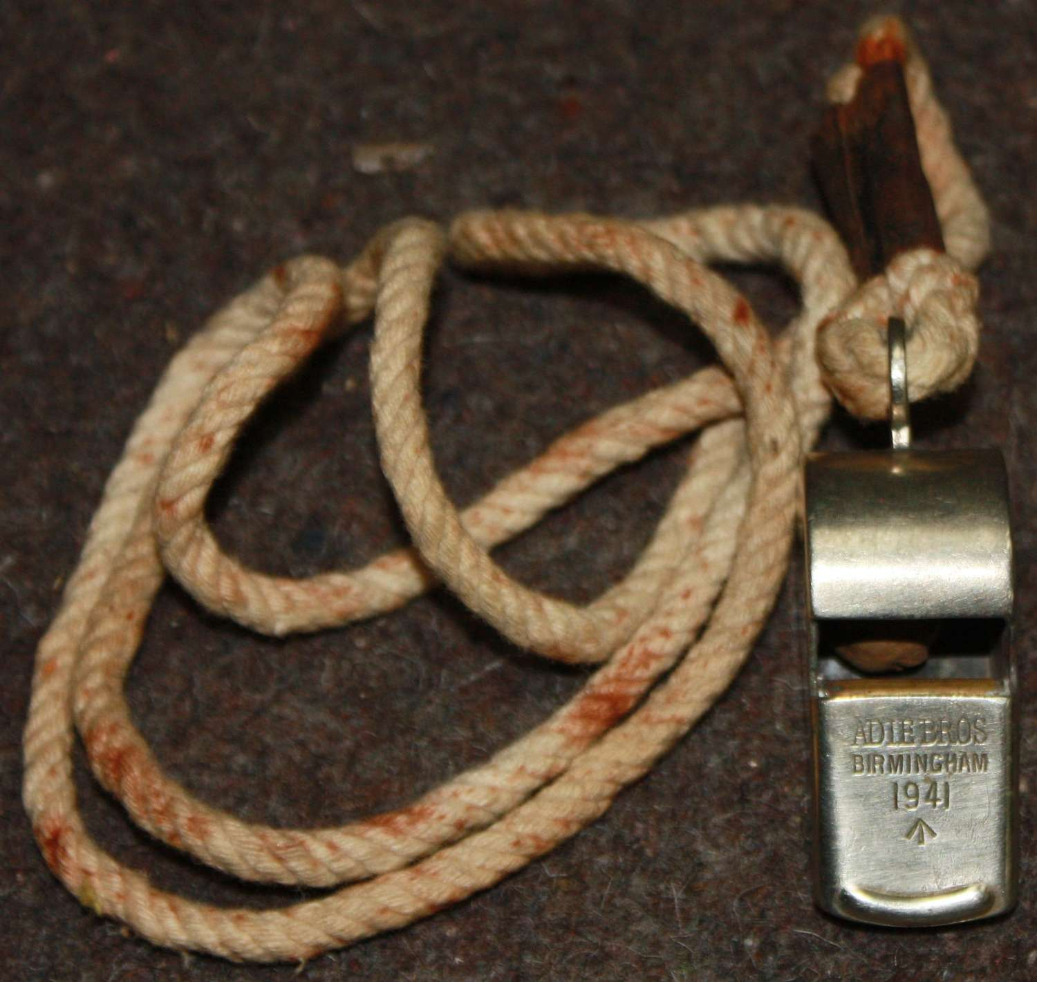 A 1941 DATED SNAIL WHISTLE WITH ITS FITTED NECK CORD