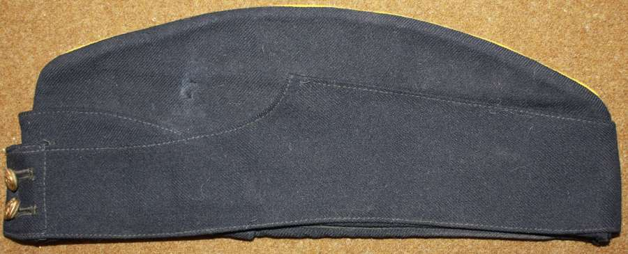 A WWII PERIOD BRITISH SIZE 7 1/8 BLACK SIDE CAP WITH YELLOW PIPING